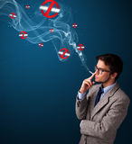 Attractive man smoking dangerous cigarette with no smoking signs Royalty Free Stock Image
