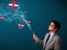 Attractive man smoking dangerous cigarette with no smoking signs Royalty Free Stock Photography