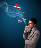 Attractive man smoking dangerous cigarette with no smoking signs Royalty Free Stock Photos