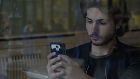 Attractive man spending time on smartphone social media while waiting for friends in restaurant stock video