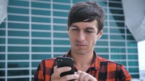 Attractive man standing near big modern office glass building and using smartphone. Red plaid shirt dressed.