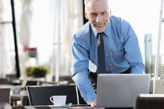 Attractive man standing near his computer Royalty Free Stock Image