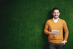 Attractive man standing over a grass wall, holding a tablet Stock Images