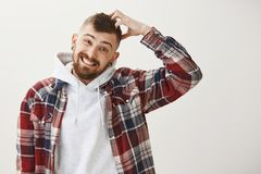 Attractive man in stylish outfit has doubts. Portrait of confused good-looking male with ear tunnels scratching head. Tilting head and smiling awkwardly, being Stock Photography