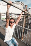 Attractive man with sunglasses hanging out in the city. Stylish man with tattoos, sunglasses and beard hanging on a metal bar with hands up with a mall, city, in Stock Image