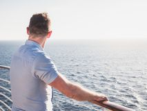 Attractive man in sunglasses on the top deck of a cruise ship. Looking out into the distance against the background of a sunset. Concept of sea travel and royalty free stock photos
