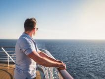 Attractive man in sunglasses on the top deck of a cruise ship. Looking out into the distance against the background of a sunset. Concept of sea travel and royalty free stock image