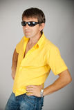 An attractive man in sunglasses and yellow shirt Royalty Free Stock Photo
