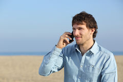 Attractive man talking on the phone on the beach Stock Photography