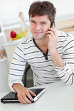 Attractive man talking on phone holding his laptop Royalty Free Stock Images