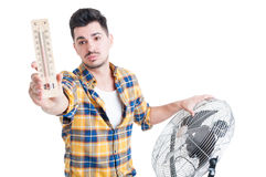 Attractive man with thermometer use electric fan to cool down Stock Images