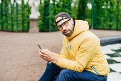 Attractive man with thick beard wearing trendy cap, yellow anorak and glasses sitting outdoors with telephone. Tourist male in cas. Ual clothes looking pensively stock photography