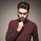 Attractive man thinking of something important. Holding his hand to his chin, looking at the camera Royalty Free Stock Images
