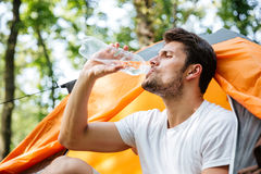 Attractive man tourist sitting and drinking water in touristic tent Royalty Free Stock Photography