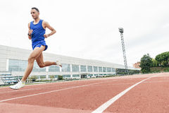 Attractive man Track Athlete Running On Track. Royalty Free Stock Images