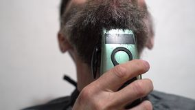 Attractive man trimming beard with electric trimmer Man using shaving machine. Hair Cutting stock footage