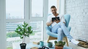 Attractive man using digital tablet sitting in chair at balcony in loft modern apartment Stock Image