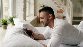 Young attractive man using tablet computer lying in bed in the morning at home. Attractive man using tablet computer lying in bed in the morning at home Royalty Free Stock Images