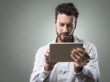 Attractive man using tablet Royalty Free Stock Images