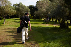 The attractive man walk to the park in clear day. Rear view of professional male golfer walking to the next hole in golf course, good golf game at sunny summer stock images