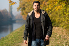 Attractive Man Walking In Autumn Forest. Young Man Walking In Forest Through The Woods Outside During Autumn Royalty Free Stock Photo