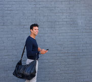 Attractive man walking with mobile phone and bag. Side portrait of an attractive man walking with mobile phone and bag Stock Images