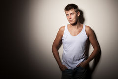 Attractive man wearing t-shirt - portrait on gray background. stock images