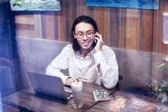 Attractive man in white shirt talking by phone and working on laptop in cafe or restaurant, having rest drinking coffee latte Royalty Free Stock Image