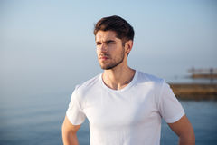 Attractive man in white t-shirt standing near the sea. Portrait of attractive young man in white t-shirt standing near the sea Stock Images