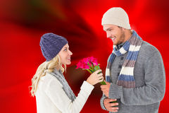 Attractive man in winter fashion offering roses to girlfriend Stock Photo