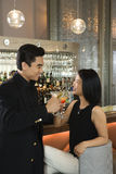 Attractive Man and Woman at Bar Having Cocktails Stock Images