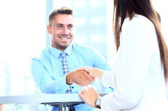 Attractive man and woman business team shaking hands Royalty Free Stock Photography
