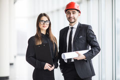 An attractive man and woman business team working construction on the building site near panoramic windows Stock Photos