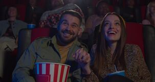 Attractive man and woman watching funny movie and smiling at movie theatre. Young couple enjoing film and talking while