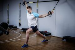 Attractive man during workout with suspension straps In The Gym Stock Photo