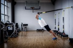 Attractive man during workout with suspension straps In The Gym Stock Image