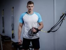 Attractive man during workout with suspension straps Royalty Free Stock Photos