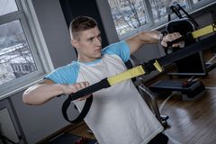Attractive man during workout with suspension straps Royalty Free Stock Photography