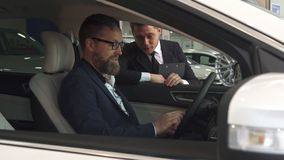Sales manager comes to the car with customer inside it stock photography