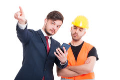 Attractive manager and engineer. Holding cellphone and pointing up isolated on white background Royalty Free Stock Photo