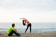 Attractive married couple engaged in stretching on the waterfront Stock Photography