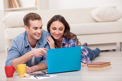 Attractive married couple is using notebook at Stock Photography
