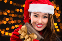Attractive x-mas lady. Close-up portrait of a cheerful x-mas lady in a Santa hat with a giftbox in hands Royalty Free Stock Photo
