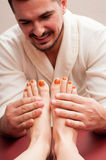 Attractive masseur smiling and massaging woman feet and soles Royalty Free Stock Photos