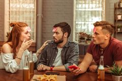 Attractive mates having fun while playing a hedbanz game. Friends at the bar. Attractive joyful cheerful nice-looking vigorous close young radiant mates having royalty free stock photography