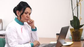 Female doctor looking upset receiving bad news working on the laptop at her clinic. Attractive mature Asian female doctor using her laptop receiving bad news stock video footage