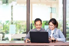 Attractive mature asian man with white stylish short beard looking at laptop computer with teenage eye glasses hipster woman in royalty free stock images