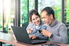 Attractive mature asian man with white stylish short beard looking at laptop computer with teenage eye glasses hipster woman in stock images