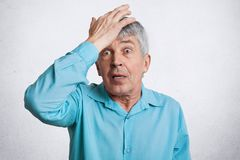 Attractive mature male with wrinkled face, keeps hand on forehead, stares at camera with suprisment, remembers about important mee. Ting, has bad memory in old Stock Photos