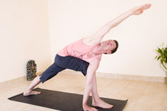 Attractive mature man doing yoga. Attractive mature man in the yoga 'Extended side angle pose - Utthita parsvakonasana stock images